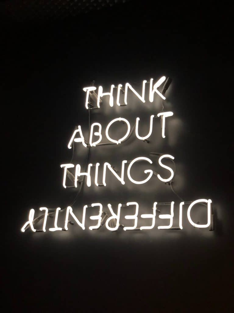 Neon letters spelling the words THINK ABOUT THINGS DIFFERENTLY with the word DIFFERENTLY being shown upside down