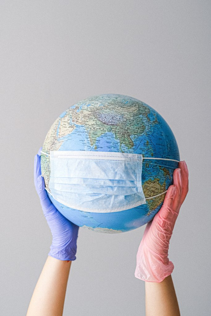 Gloved hands raising a round globe with a mask attached to it