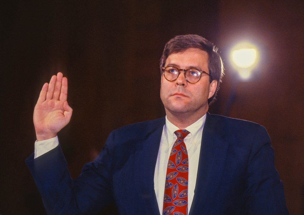Bill Barr with his right arm raised swearing an oath