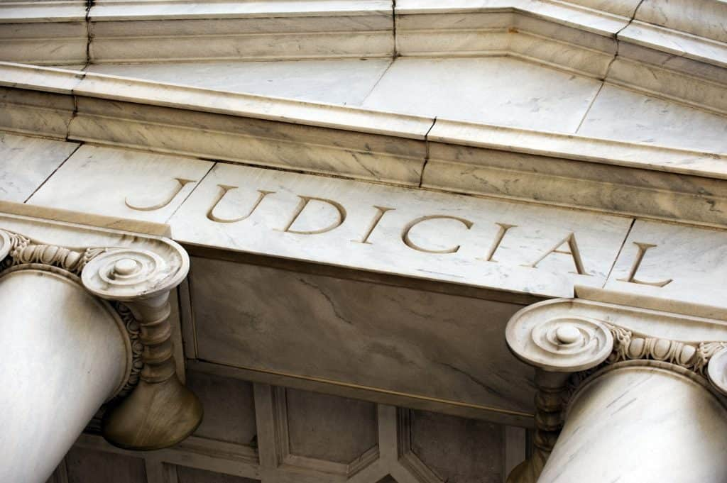 The front of a large stone building with the word Judicial carved in it