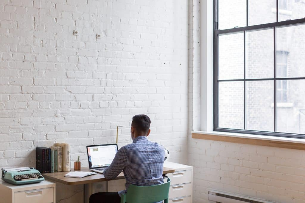 A man working at home on a laptop facing a white brick wall