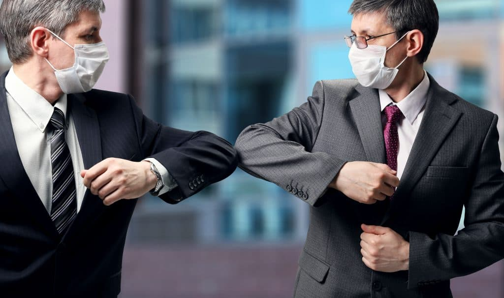 2 lawyers with masks on touching elbows in greeting instead of shaking hands
