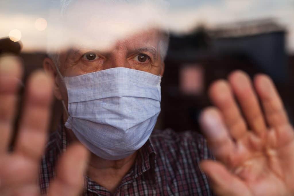 An older man wearing a mask waving through a window