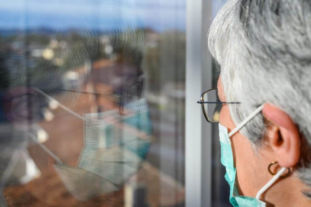 An older woman wearing a mask looking through a window