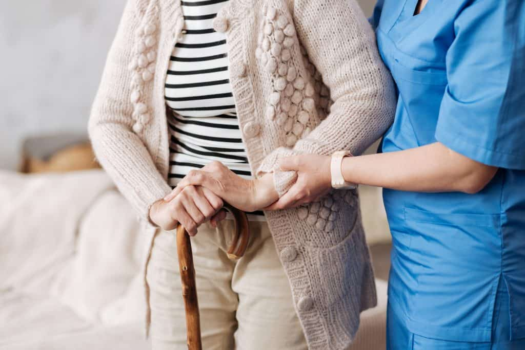 A nurse helping an older woman walk with her cane